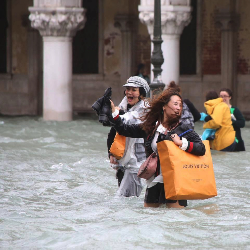Shopping while they drawn. | Tourist with Louis Vuitton bag wading through flooded Venice.
